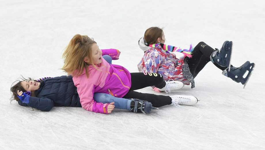Norwalk's Emma Seferidis, left, 8, Stamford's Addison Clear, center, 9, and Lyla Sutlif, 8, take a spill at the Steven & Alexandra Cohen Skating Center at Mill River Park in Stamford, Conn. Sunday, Dec. 9, 2018. The Mill River Park Collaborative will offer activities for school-aged children on Monday and Tuesday. Photo: Tyler Sizemore / Hearst Connecticut Media / Greenwich Time
