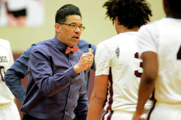 Summer Creek Head Coach Kenneth Coleman, left, pumps up Bulldogs guard Javon Jackson (3) against Dobie during their District 22-6A matchup at SCHS on Feb. 12, 2019.