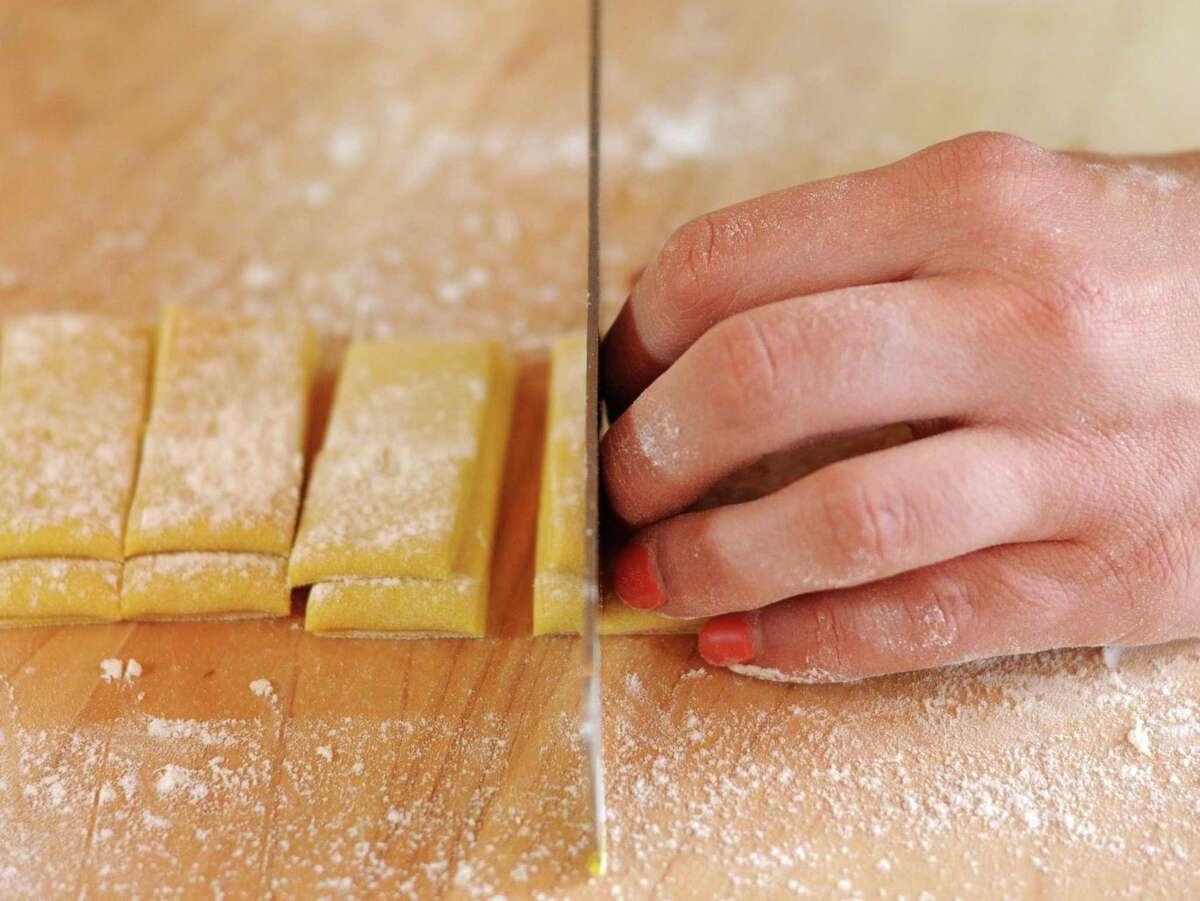 Elena D'Agostino cuts pasta dough into pappardelle.