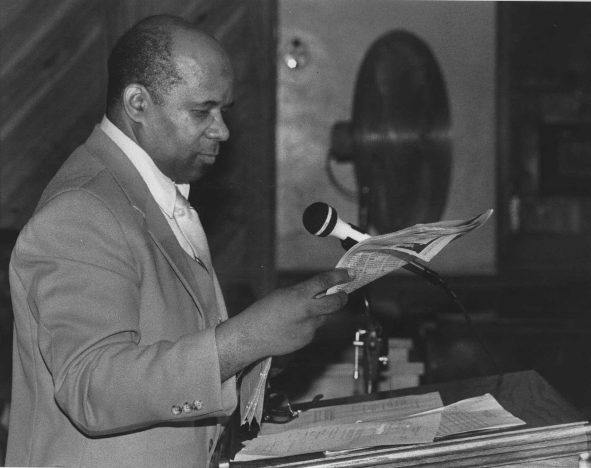 St. John's Church of God in Christ, Albany, New York - Reverend McKinley Johnson reads excerpt from the South End Scene. August 11, 1974 (Hai Do/Times Union Archive)
