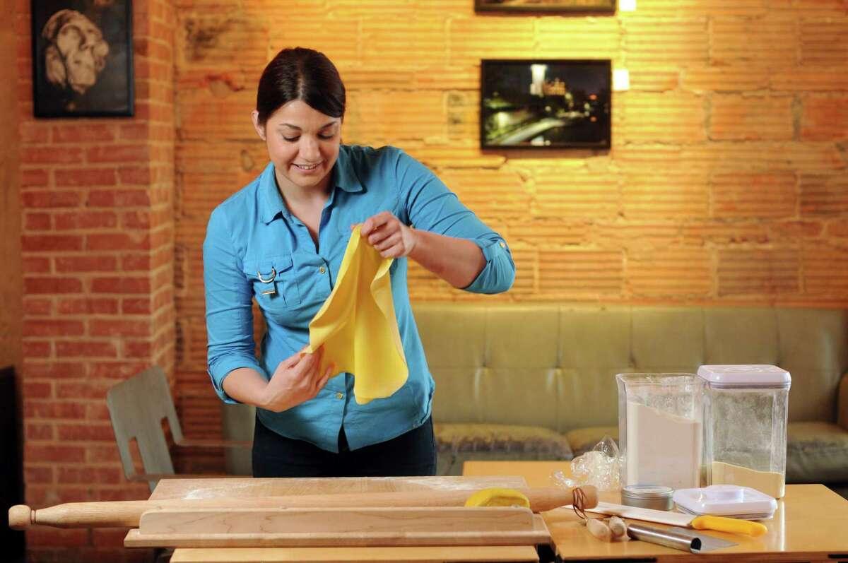 Elena D'Agostino rolls out a sheet of pasta dough.