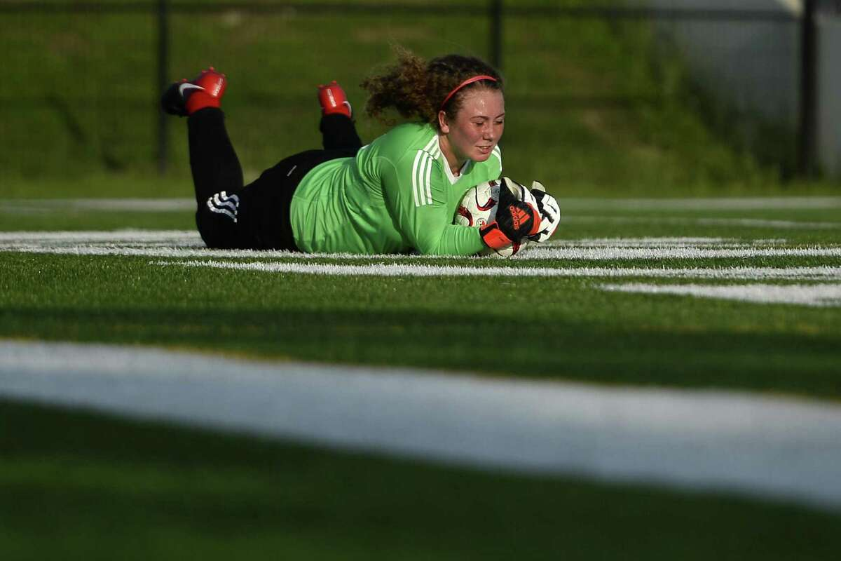 Huffman goalkeeper Taylor Symons makes a save against Jasper in a girls soccer playoff game at the Thomas Center on Tuesday evening. Photo taken Tuesday 4/3/18 Ryan Pelham/The Enterprise