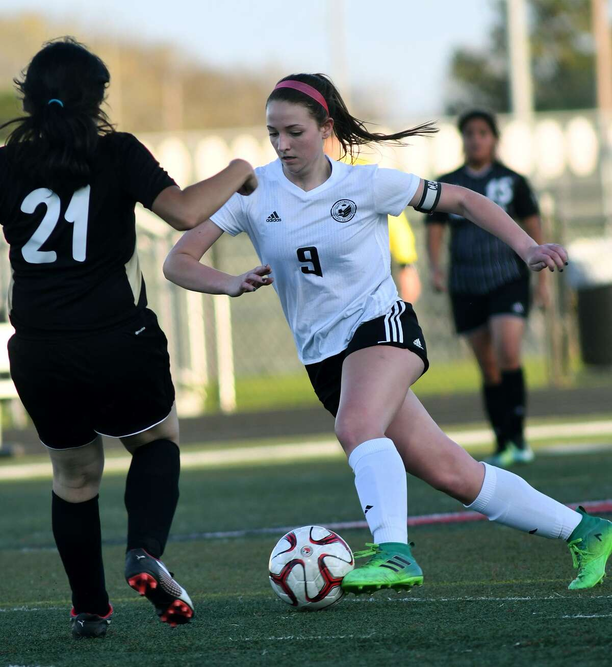 Huffman sophomore captain Sydney Bray (9) works the ball against Anahuac's Ana Chavez (21) during their district matchup at Falcon Stadium on March 2, 2018. (Photo by Jerry Baker/Freelance)