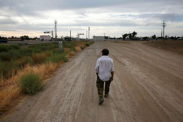 """Mart'n Hernandez Mena, 50, walks down the dirt road leading away from the shantytown towards a corner store in the early morning Sept 28, 2015 outside of Mendota, Calif. Mena has lived for a year and a half in the canal bed after he could no longer afford rent in town. Mena has lived in the U.S. for 12 years and has four grown children in Mexico, where he is from. He used to have steady farm work, starting with water melons, cantaloupes, grapes, tomatoes and pomegranate. The last few years he worked in pistachios and almonds and it was five years ago that he last had steady work as an employee. Since then, he says, it has been harder to find work. Mena mostly survives by doing work for others who live in the shantytown, such as building and fixing things for them. Sometimes he finds odd jobs in Mendota working for people in town. """"I keep thinking and hoping of finding ways to get out of this canal. Once I�m free from that, I can focus on other things.� Mena said in Spanish. �All your energy goes to just getting by here."""" Those who live in the encampment and others from Mendota say that there have been a small number of structures in the canal bed for years. But as California entered into the third and fourth years of one of the worst droughts in its modern history, the shantytown bloomed to nearly 30 structures. Mendota has a population of about 11,500 people with more than 40 percent of the population living below the poverty line. Steady work has become more and more difficult to find for community members who depend heavily on the agriculture industry. After months of litigation, Westlands Water District evicted the shantytown residents in November."""