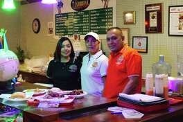 Sherida Mohamed, center, works with husband Naseer and daughter Sherina at D' Caribbean Curry Spot in Pearland. She says she had started cooking foods that she missed from her native Trinidad and opened the restaurant 12 years ago after finding that area residents liked it.