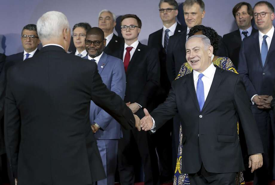 Vice President Mike Pence and Israeli Prime Minister Benjamin Netanyahu (right) shake hands at a two-day international conference on the Mideast. Photo: Michael Sohn / Associated Press