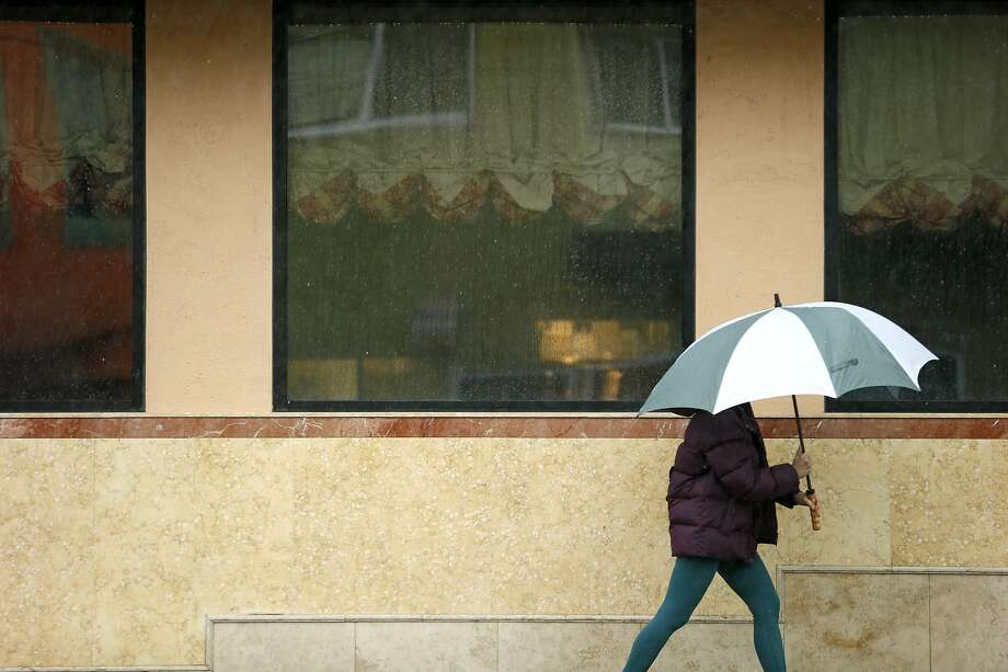 FILE -- A woman makes her way through a storm on Wednesday, Feb. 13, 2019, in San Francisco, Calif. The rain is predicted to continue Saturday into Sunday, with intermittent rain breaking up bouts of sunshine, making for an unpredictable day of weather. Photo: Santiago Mejia / The Chronicle