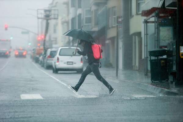 A man leaps over the flooded street corner as he runs the crosswalk through a storm on Wednesday, Feb. 13, 2019, in San Francisco, Calif.