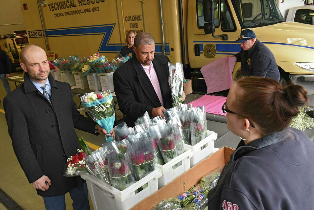 Michael Sollohub of Niskayuna, left, gets rose care advice from Colonie firefighter Andrea Goes, right, as Dave Brown, President and CEO of the Capital District YMCA, center, picks out roses for his wife at the annual Valentines Day rose sale at the Colonie Fire Company on Wednesday, Feb. 13, 2019 in Colonie, N.Y. Michael was buying roses for his wife and daughter. (Lori Van Buren/Times Union)