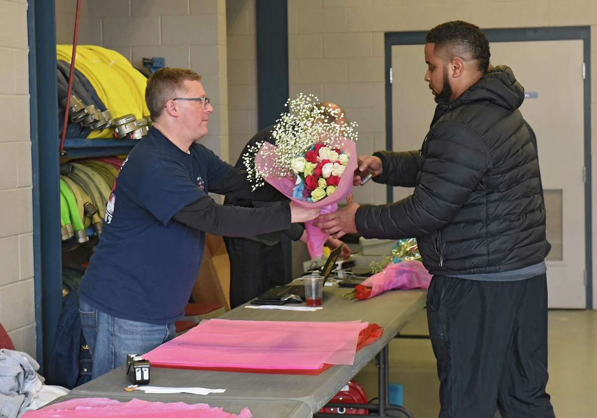 Daiwan Perry of Albany, right, buys flowers for his mother from Colonie firefighter Peter Chudzinski at the annual Valentines Day rose sale at the Colonie Fire Company on Wednesday, Feb. 13, 2019 in Colonie, N.Y. (Lori Van Buren/Times Union)