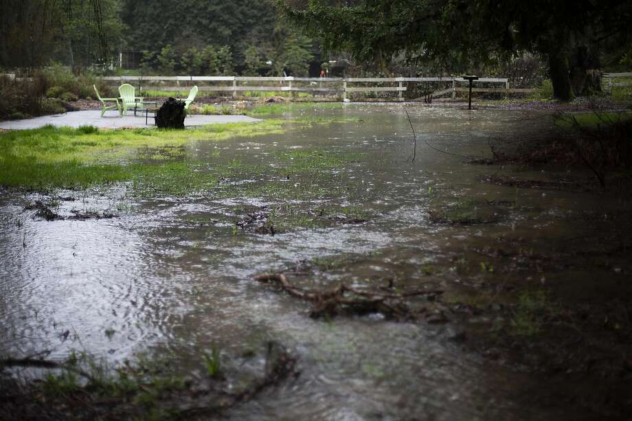 "A large puddle and patio chairs in a yard in Guerneville after an""atmospheric river"" storm brought heavy rainfall to the Bay Area overnight, in Guerneville, California, February 13th, 2019. Photo: Talia Herman /"