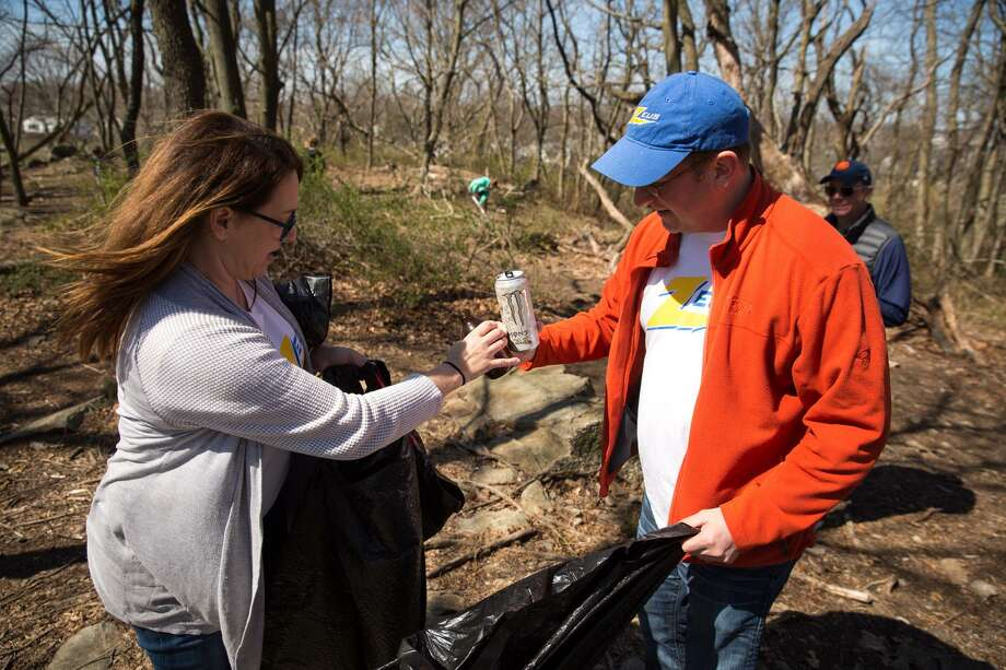 Jen Cunniffe and Nate Gilbertson pick up trash with the Zeus Swim Team at Taylor Farm during the Mayor's Citywide Earth Day Spring Cleanup in Norwalk, Conn. on Saturday, April 21, 2018. Photo: Chris Palermo / For Hearst Connecticut Media / Norwalk Hour Freelance