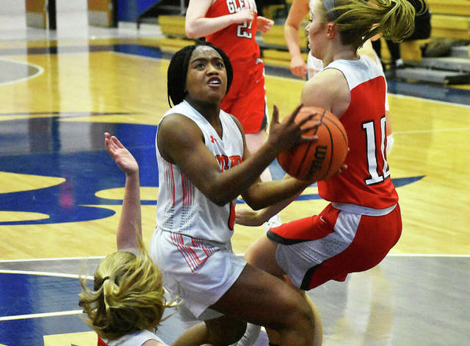 Edwardsville junior point guard Quierra Love runs through two Chatham Glenwood defenders on her way to the basket. Photo: Matt Kamp/Intelligencer