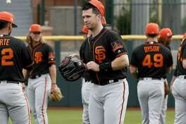 San Francisco Giants catcher Buster Posey takes the field during a baseball spring training practice, Wednesday, Feb. 13, 2019, in Scottsdale, Ariz. (AP Photo/Matt York)
