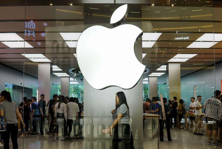 Shoppers seek Apple products in a Shanghai store. A former corporate lawyer has been charged with trading Apple stock using inside information. Photo: Chandan Khanna / AFP / Getty Images 2017