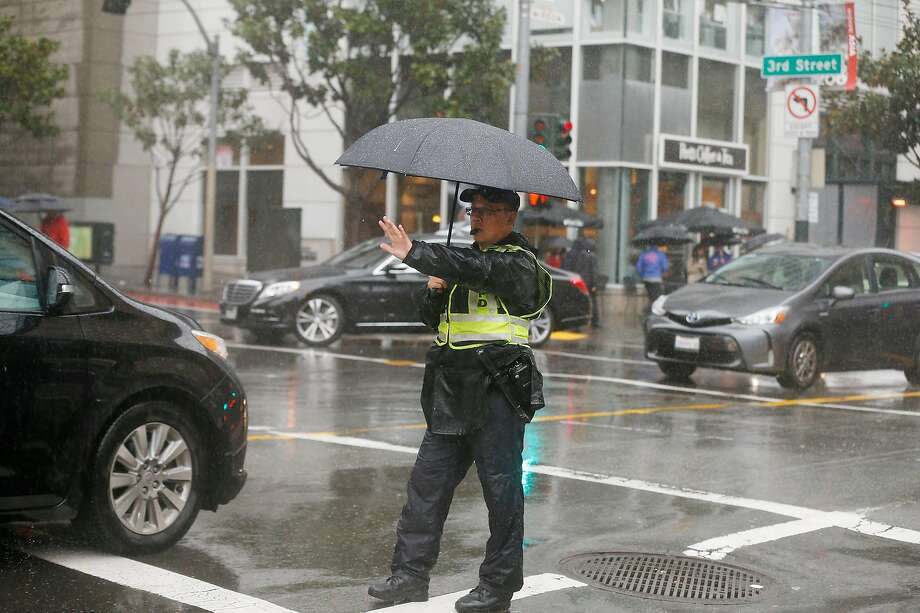 Officer Eddie Wu works in the rain directing traffic  in the intersection of Mission and Third Streets on Wednesday, February 13,  2019 in San Francisco, Calif. Photo: Lea Suzuki / The Chronicle
