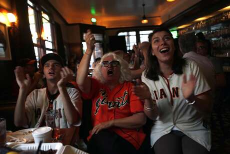 As the Giants score a run in their wild card playoff game, Surma Mauro (center) and her children Raphael (left) and Saskia (right) celebrate while watching the game on television at the Dogpatch Saloon on 3rd Street in San Francisco, Calif. on Wednesday, October 1, 2014. Surma Mauro moved to the Dogpatch neighborhood in 1981.