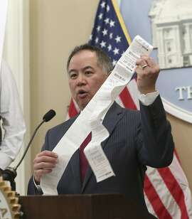 Assemblyman Phil Ting, D-San Francisco, displays a long paper receipt as he discusses his bill to require businesses to offer electronic receipts, Tuesday, Jan. 8, 2019, in Sacramento, Calif. Under the legislation customers could receive a paper receipt on request.