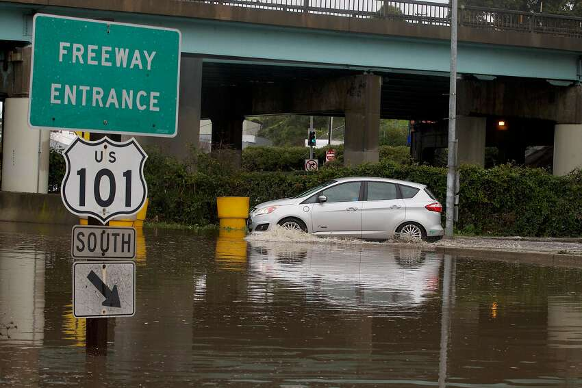 A car navigates its way through a flooded area to a freeway onramp along Alemany Boulevard on Wednesday, February 13, 2019 in San Francisco, Calif.