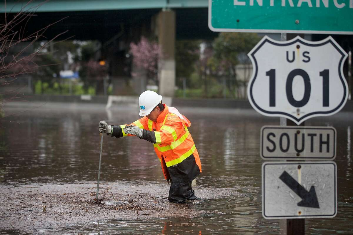 Jack Lam,a Caltrans equipment operator, works at a freeway onramp along Alemany Boulevard to unclog a drain in a flooded area closed to traffic on Wednesday, February 13, 2019 in San Francisco, Calif.