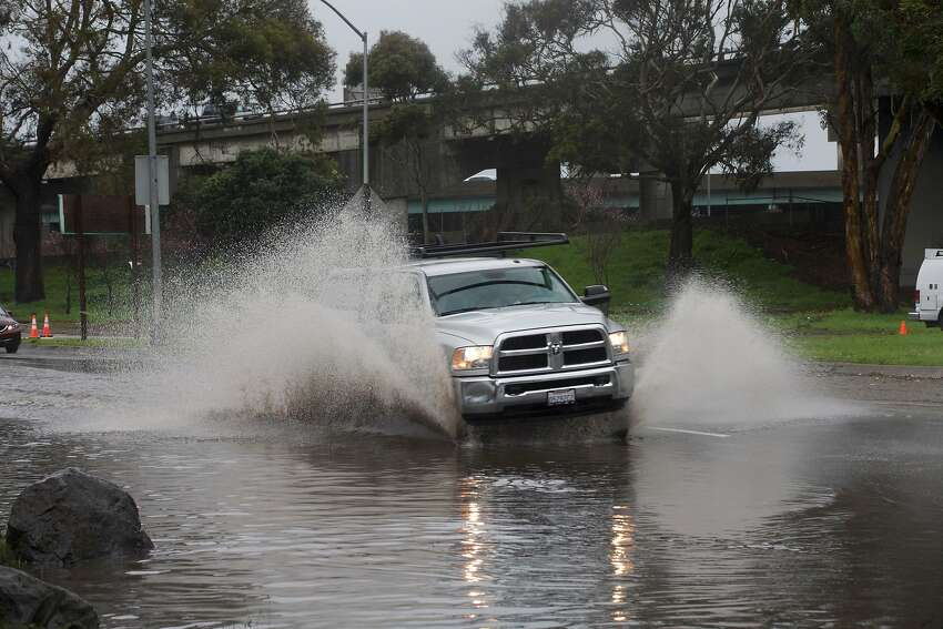 A car navigates its way through a flooded area along Alemany Boulevard on Wednesday, February 13, 2019 in San Francisco, Calif.