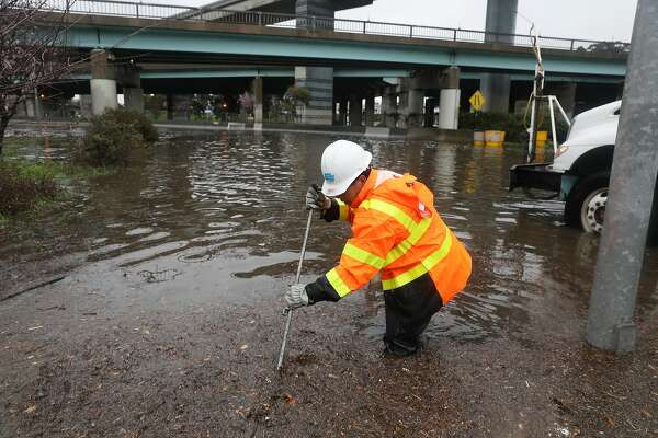 Jack Lam, CalTrans equipment operator, works at a freeway onramp along Alemany Boulevard to unclog a drain in a flooded area closed to traffic on Wednesday, February 13, 2019 in San Francisco, Calif.