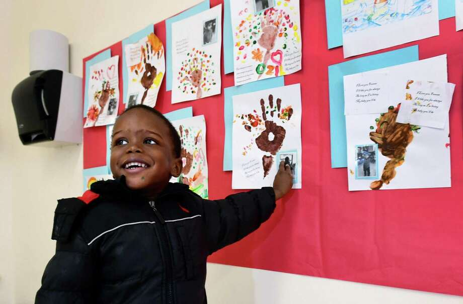 Three-year-old Samroujed Michel points out his masterpiece as the Greater Norwalk Head Start hosts an art fair Wednesday, featuring art created by the program's children and their parents and exhibited at the former Ben Franklin School in Norwalk. The theme of the artwork is love and friendship. Photo: Erik Trautmann / Hearst Connecticut Media / Norwalk Hour