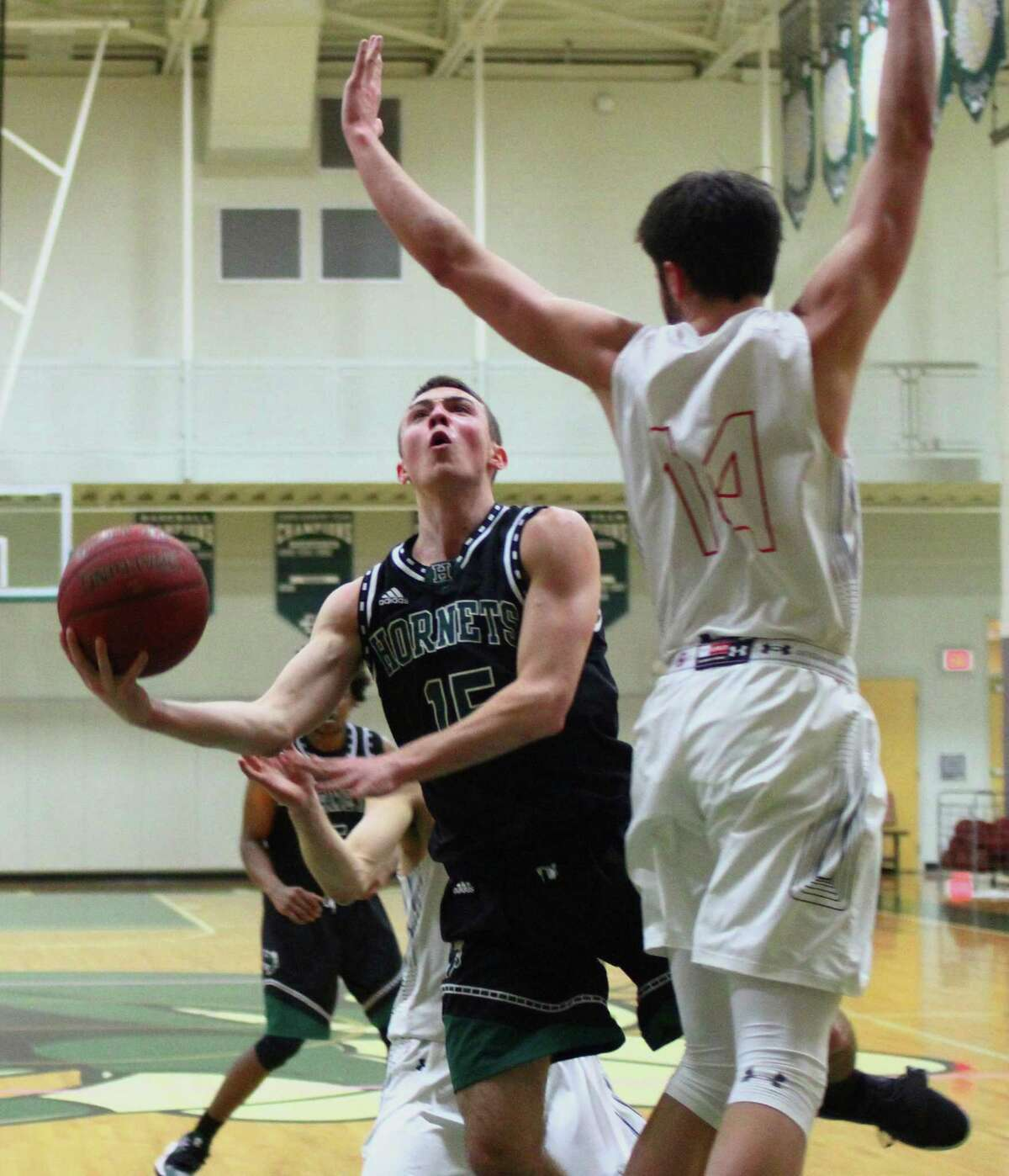 Hamden Hall's Jackson Benigni (15) lays up the ball as Greens Farms Academy's Greg Lawrence (14) defends during basketball action in Hamden, Conn., on Wednesday Feb. 13, 2019.