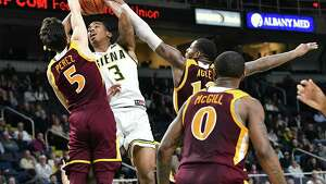 Siena's Manny Camper goes up for a shot guarded by Iona's Ben Perez, left, and Tajuan Agee during a basketball game at the Times Union Center on Wednesday, Feb. 13, 2019 in Albany, N.Y. (Lori Van Buren/Times Union)
