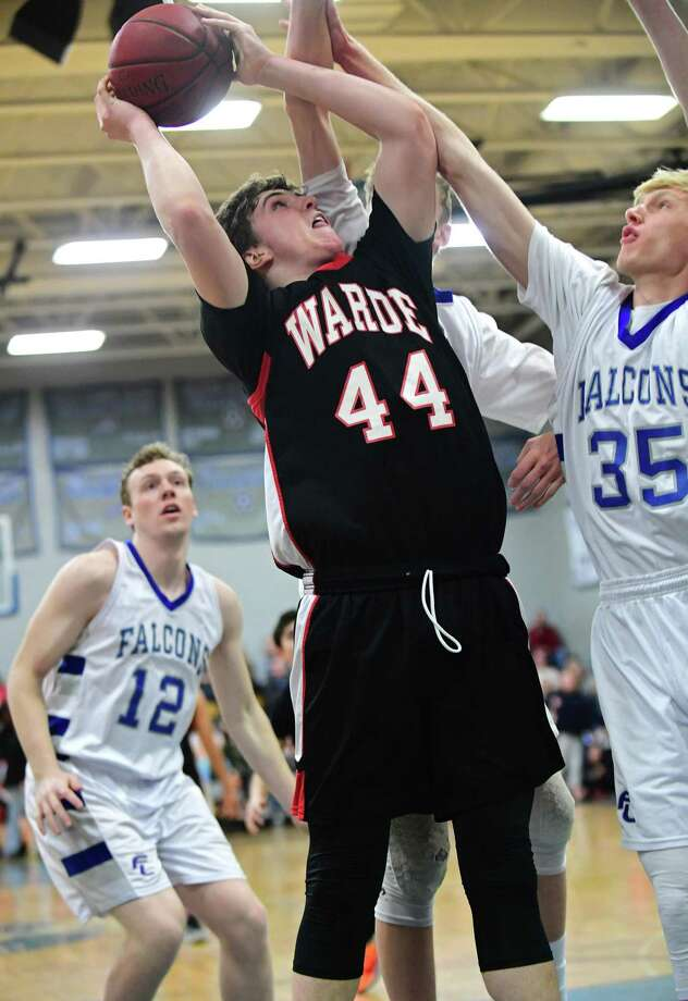 Warde's Jack McKenna goes to hoop past Ludlowe's Jake Northrop (12) and Rowan Keesser during their FCIAC game Wednesday night in Fairfiled. Photo: Erik Trautmann / Hearst Connecticut Media / Connecticut Post