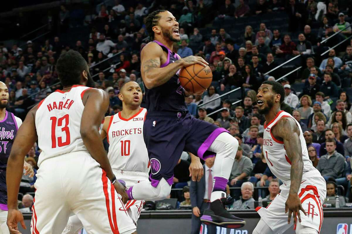 Minnesota Timberwolves' Derrick Rose, center, goes airborne for a layup as Houston Rockets' James Harden, left, Eric Gordon and Michael Carter-Williams, right, watch in the first half of an NBA basketball game, Wednesday, Feb. 13, 2019, in Minneapolis. (AP Photo/Jim Mone)