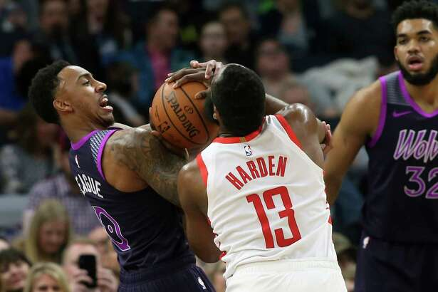 Houston Rockets' James Harden (13) and Minnesota Timberwolves' Jeff Teague battle for the ball as Timberwolves' Karl-Anthony Towns (32) looks on in the first half of an NBA basketball game, Wednesday, Feb. 13, 2019, in Minneapolis. (AP Photo/Jim Mone)