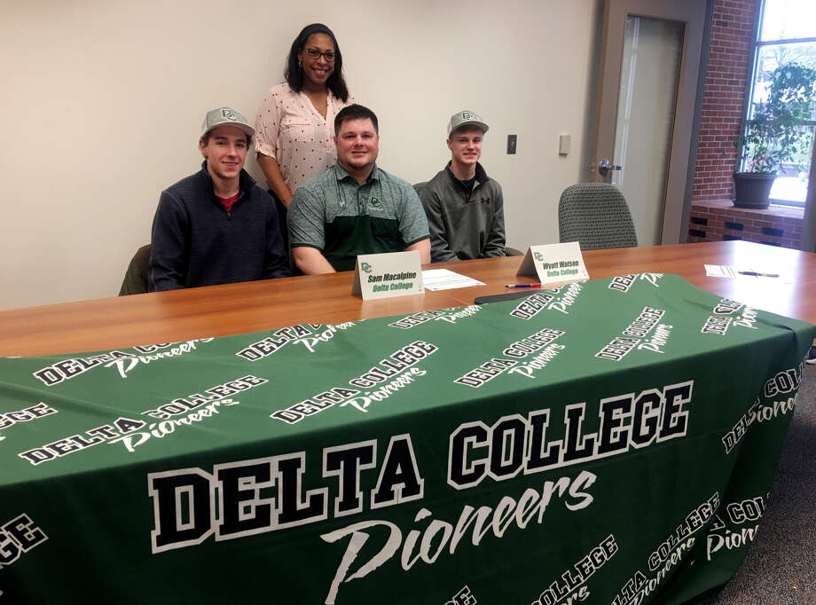 Bad Axe's Sam MacAlpine (left) and Deckerville's Wyatt Watson (right) are joined by Delta College golf coach Kyle Middleton (sitting) and Delta College athletic director Dionne McCollum, after the duo signed their letter of intent to play golf for Delta. (Courtesy Photo)