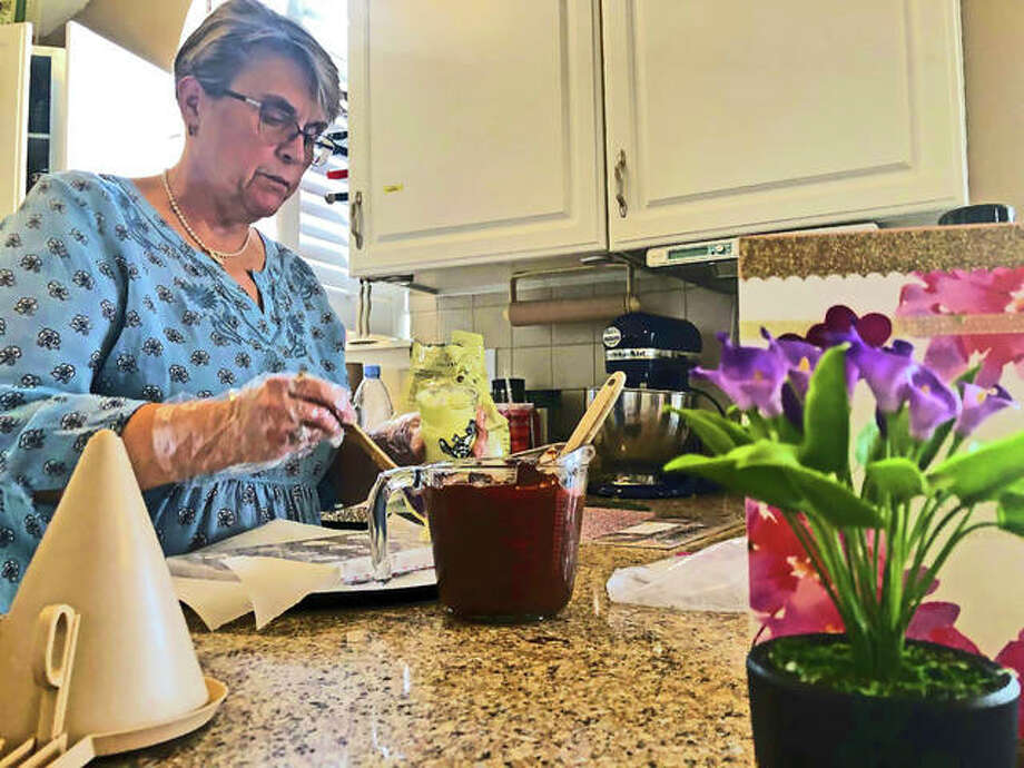 Edwardsville businesswoman Jan Rock spoons chocolate into a heart-shaped mold at her home in the kitchen Wednesday, creating pieces just in time for Valentine's Day. Photo: Brittany Johnson | The Intelligencer