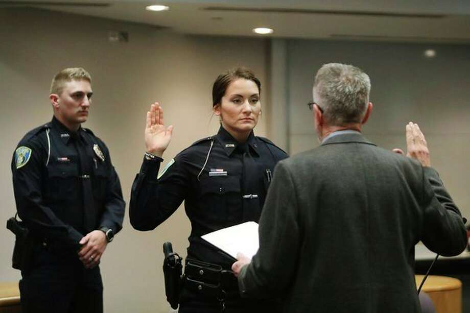Haylee Porterfield, center, raises her hand while giving the oath during a swearing-in ceremony for Midland's two newest police officers, Porterfield and Nathan Neuman, left, on Tuesday at City Hall. For more photos, go to www.ourmidland.com. (Katy Kildee/kkildee@mdn.net)