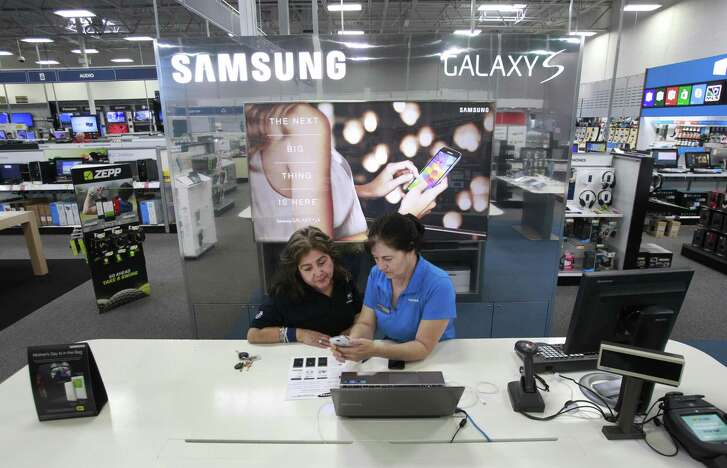 Customer Linda Avila, left, works with Donna Becerril, right, Samsung store lead, at the Samsung kiosk in Best Buy, 9670 Old Katy Road, Tuesday, May 13, 2014, in Houston. ( Melissa Phillip / Houston Chronicle )