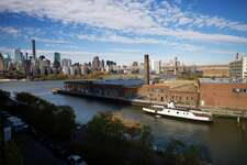 FILE- In this Nov. 7, 2018, file photo, a rusting ferryboat is docked next to an aging industrial warehouse on Long Island City's Anable Basin in the Queens borough of New York. Amazon said Thursday, Feb. 14, 2019, that it is dropping New York City as one of its new headquarter locations.
