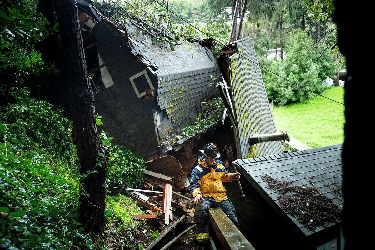 A home rests on its side after sliding dozens of yards down a Sausalito, Calif., hillside on Thursday, Feb. 14, 2019. The mudslide, which also destroyed at least two vehicles, left the home covered by trees near Crescent Ave.