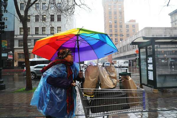 """Jazz singer and painter Sybil Carpenter, aka Sheebah Maceo, pushes a cart of groceries in the rain after getting off of a bus on Broadway to arrive to another one in Downtown Oakland, Calif., on Wednesday, February 13, 2019. Carpenter forgot her cell phone at her apartment and had to take public transportation from Oakland to Berkeley and back. """"I think we need to share umbrellas during the storm of life,"""" Carpenter said. """"Life is filled with challenges -- big and small. We don't need to feel defeated."""""""