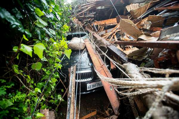 Debris covers a BMW following a landslide above Crescent Ave. in Sausalito, Calif., on Thursday, Feb. 14, 2019. The slide destroyed at least two vehicles and a home.