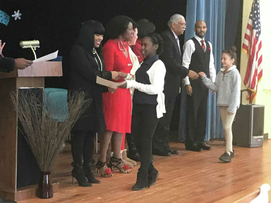 Ross/Woodward fourth grade student Christianne Charles shakes hands with the school's attendance committee as she receives a certificate for perfect attendance this year. Photo: Brian Zahn / Hearst Connecticut Media