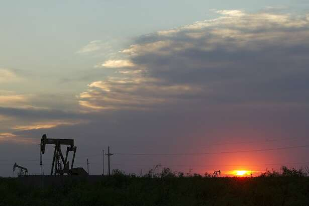 The sun sets behind a group of pump jacks Wednesday, June 1, 2011, outside of Midland. ( Brett Coomer / Houston Chronicle )