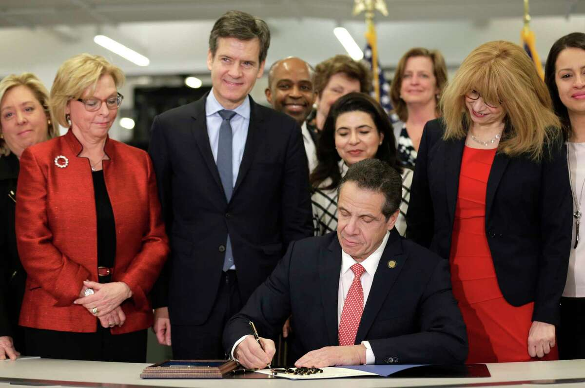 New York Gov. Andrew Cuomo, center, signs the Child Victims Act in New York, Thursday, Feb. 14, 2019. Cuomo has signed into law long-sought legislation that extends the statute of limitations so sexual abuse victims can have more time to seek criminal charges or file lawsuits.