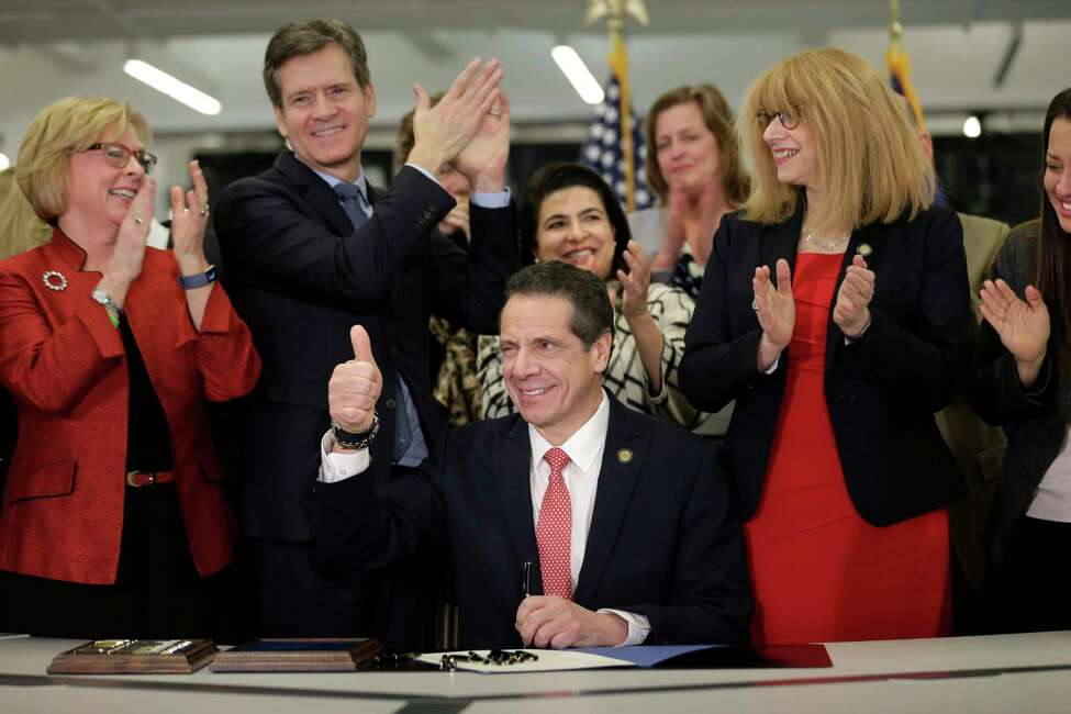 New York Gov. Andrew Cuomo, center, winks and gives a thumbs-up after signing the Child Victims Act in New York, Thursday, Feb. 14, 2019. Cuomo has signed into law long-sought legislation that extends the statute of limitations so sexual abuse victims can have more time to seek criminal charges or file lawsuits.