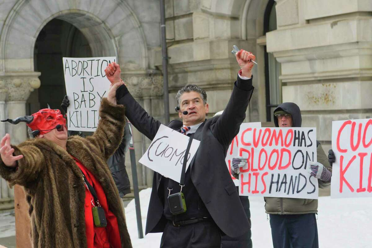 Pro-life leader, Randall Terry, left, dressed as Satan, raises the hand of Gary Boisclair, who plays the part of Governor Andrew Cuomo during a street theatre performance outside the Capitol on Thursday, Feb. 14, 2019, in Albany, N.Y. The stop in Albany was part of Terry's ?Christ, Cuomo, and Satan Tour to call attention to what he says is New York State's aggressive promotion of late term abortion. (Paul Buckowski/Times Union)