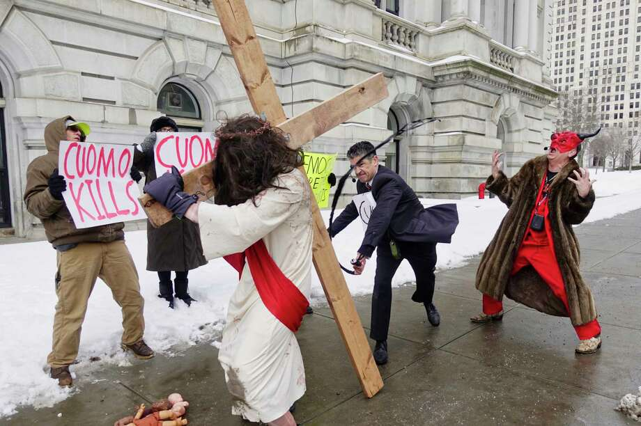Gary Boisclair, center, playing the part of Governor Andrew Cuomo, strikes Alexander Lovato, who plays the part of Jesus, as pro-life leader Randall Terry, right, plays the part of Satan, during a street theatre performance outside the Capitol on Thursday, Feb. 14, 2019, in Albany, N.Y. The stop in Albany was part of Terry's ?Christ, Cuomo, and Satan Tour to call attention to what he says is New York State's aggressive promotion of late term abortion.    (Paul Buckowski/Times Union)     (Paul Buckowski/Times Union) Photo: Paul Buckowski, Albany Times Union / (Paul Buckowski/Times Union)
