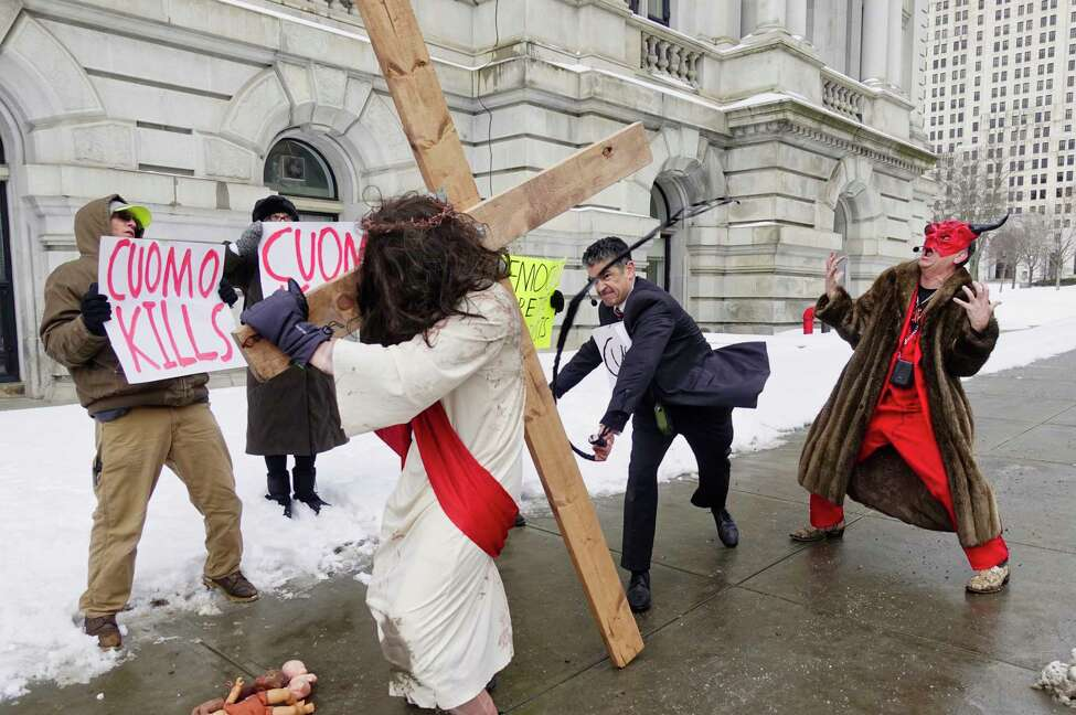 Gary Boisclair, center, playing the part of Governor Andrew Cuomo, strikes Alexander Lovato, who plays the part of Jesus, as pro-life leader Randall Terry, right, plays the part of Satan, during a street theatre performance outside the Capitol on Thursday, Feb. 14, 2019, in Albany, N.Y. The stop in Albany was part of Terry's ?Christ, Cuomo, and Satan Tour to call attention to what he says is New York State's aggressive promotion of late term abortion. (Paul Buckowski/Times Union) (Paul Buckowski/Times Union)