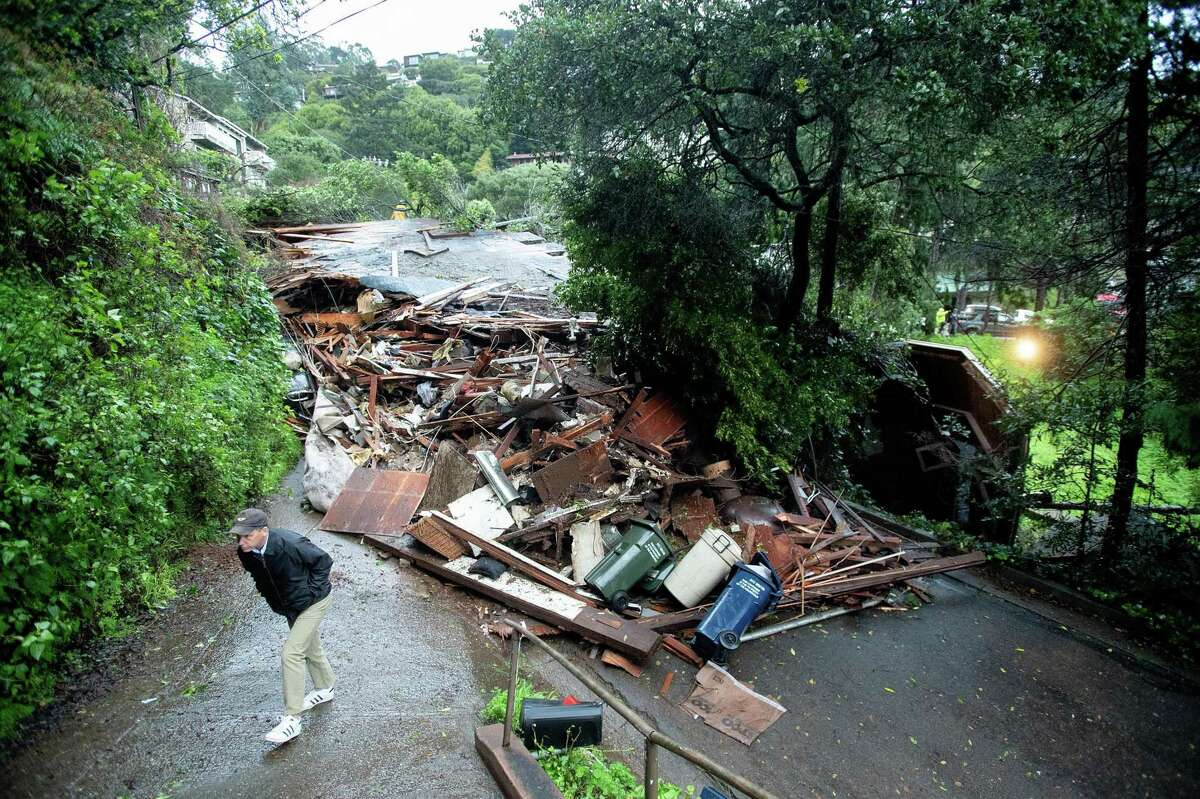 Rob Bagot walks past debris blocking Crescent Avenue after a mudslide in Sausalito that destroyed a home and at least two vehicles.