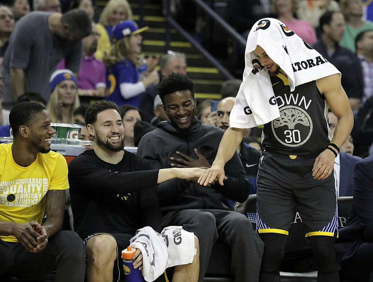Klay Thompson (11) and Stephen Curry (30) high five after Jonas Jerebko (21) hit a three pointer in the first half as the Golden State Warriors played the Miami Heat at Oracle Arena in Oakland, Calif., on Sunday, February 10, 2019.