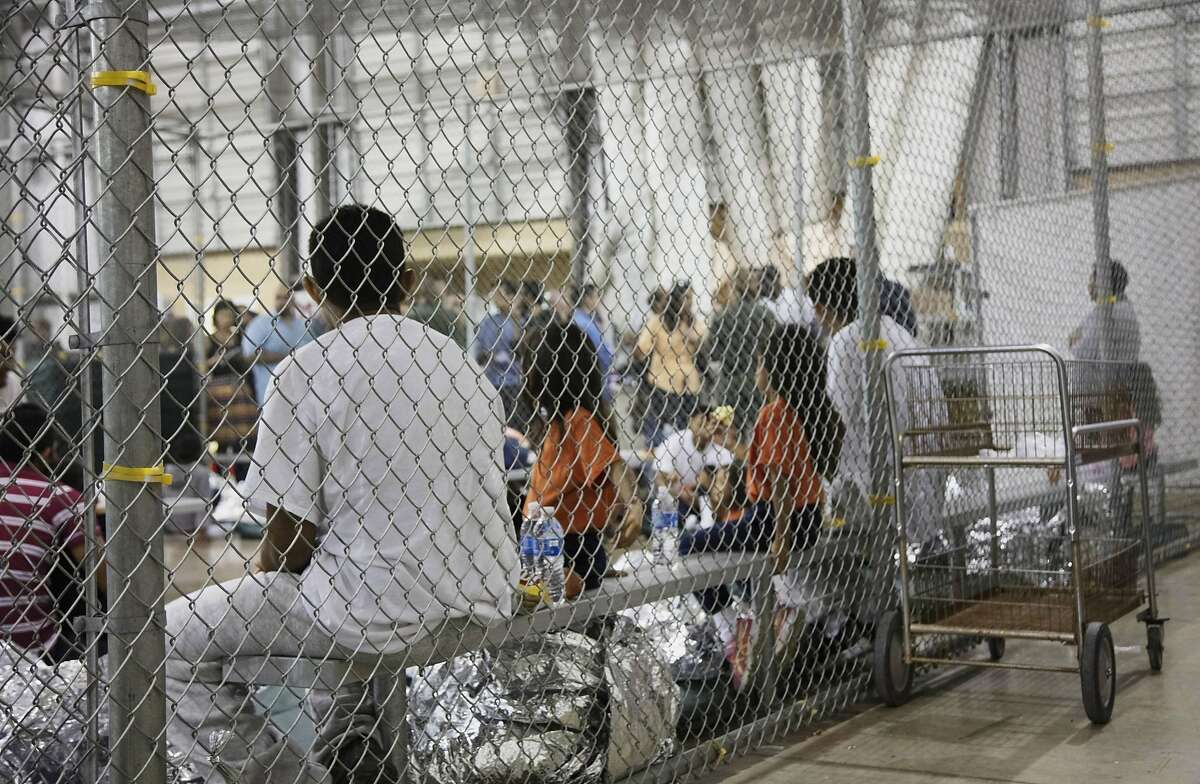 FILE - In this June 17, 2018 file photo provided by U.S. Customs and Border Protection, people who've been taken into custody related to cases of illegal entry into the United States, sit in one of the cages at a facility in McAllen, Texas. Some immigrant youth looking to start over in the United States after fleeing abusive homes are seeing their applications for green cards rejected because the Trump administration says they're too old. Immigrant advocates have filed lawsuits in New York and California and said hundreds of young people could be affected by the change. (U.S. Customs and Border Protection's Rio Grande Valley Sector via AP, File)